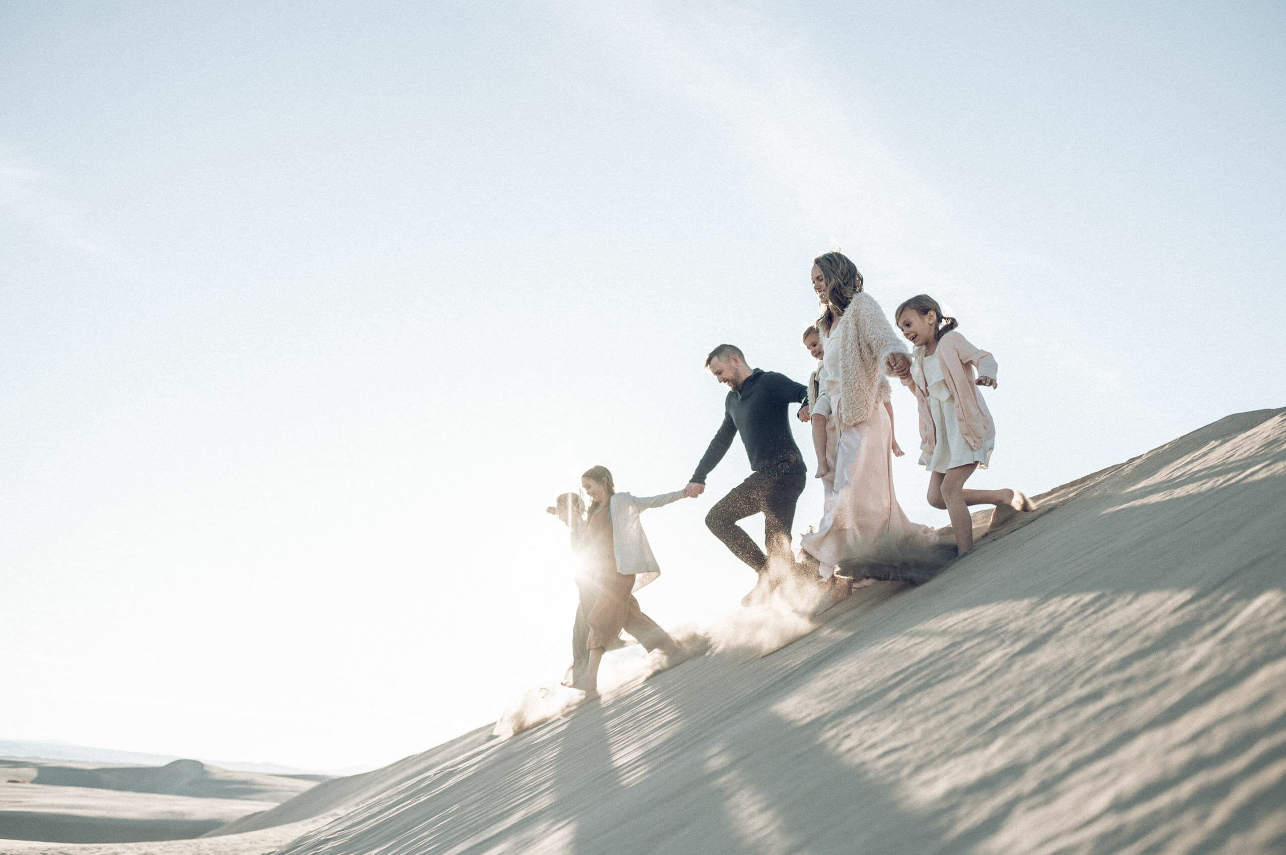 Family running on a sand dune